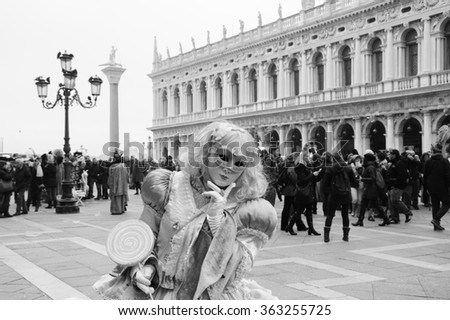 VENICE, ITALY - FEBRUARY 14, 2015: Candy Mask in St Mark's Square square and tourist crowd during the Carnival. The Carnival in Venice is annual event which ends on Shrove Tuesday. - stock photo