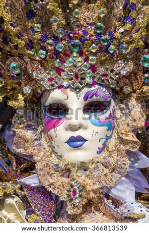 VENICE, ITALY - FEBRUARY 16, 2015: Close up of a beautiful carnival mask made of gems and beads during the Carnival of Venice in Italy. - stock photo