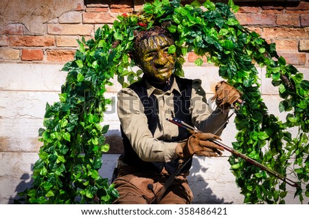 Venice, Italy - February 26, 2011: During the carnival street performer in Piazza San Marco in Venice. Spectacular musician disguised as tree entertains tourists with a musical instrument unusual. - stock photo
