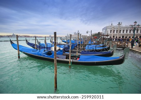 VENICE, ITALY - FEBRUARY 15 : Gondolas moored in the water canal in front of people walking on Riva degli Schiavoni on February 15th, 2014 in Venice, Italy.
