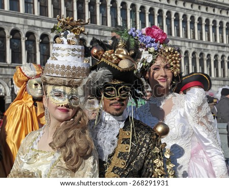 VENICE, ITALY - FEBRUARY 8, 2015: Group of masked persons in beautiful ornate costume on San Marco Square during the Carnival in Venice, Italy. - stock photo