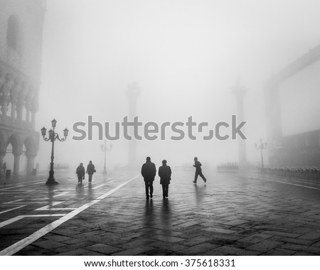 VENICE, ITALY -  8 FEBRUARY 2011:  Monochrome image of couples walking and a jogger running through a very foggy St Marks Square, early morning in Venice.  Contemporary street scenes of Venice, Italy