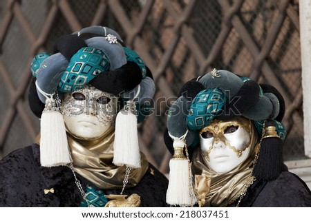 Venice, Italy - February 11, 2012: People posing wearing a typical Carnival mask in St. Mark's Square - stock photo