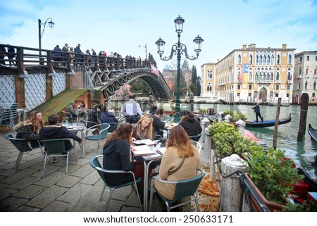 VENICE,ITALY-FEBRUARY 15:People sitting in a coffee shop next to the Ponte dell Accademia bridge on February 15th,2014 in Venice, Italy. Ponte dell Accademia is one of the four bridges on grand canal. - stock photo