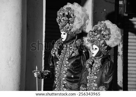 VENICE, ITALY - FEBRUARY 16, 2015:Two masks  in St Mark's Square during traditional Carnival. Carnival is annual event which ends on Shrove Tuesday.