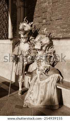 VENICE, ITALY - FEBRUARY 16, 2015:Two masks in sunlight near Doge's Palace in St Mark's Square during traditional Carnival. The Carnival in Venice is annual event which ends on Shrove Tuesday.