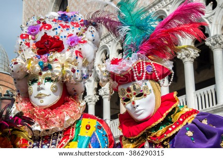 VENICE, ITALY - FEBRUARY 15, 2015:Two models disguised with colorful carnival costumes, posing in San Marco square during the Carnival of Venice. - stock photo