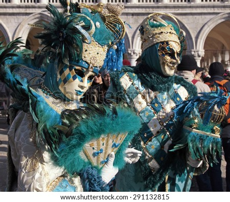 VENICE, ITALY - FEBRUARY 8, 2015: Two unidentified masked persons in costume on San Marco Square during the Carnival in Venice, Italy. Selective focus - stock photo