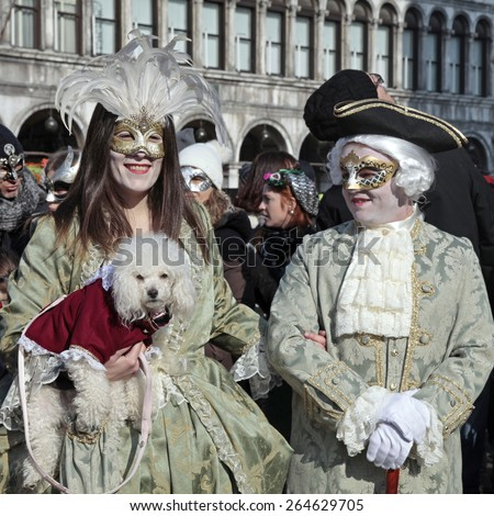 VENICE, ITALY - FEBRUARY 8, 2015: Two unidentified masked persons in costume with small dog on San Marco Square during the Carnival in Venice, Italy. - stock photo