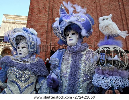 VENICE, ITALY - FEBRUARY 8, 2015: Two unidentified masked persons in magnificent lilac medieval costume on San Marco Square during the Carnival in Venice, Italy. - stock photo