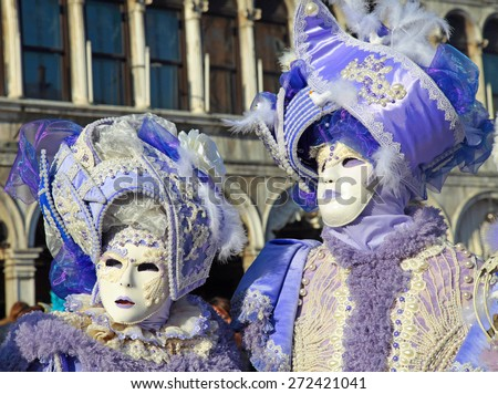 VENICE, ITALY - FEBRUARY 8, 2015: Two unidentified masked persons in ornate lilac medieval costume on San Marco Square during the Carnival in Venice, Italy. - stock photo