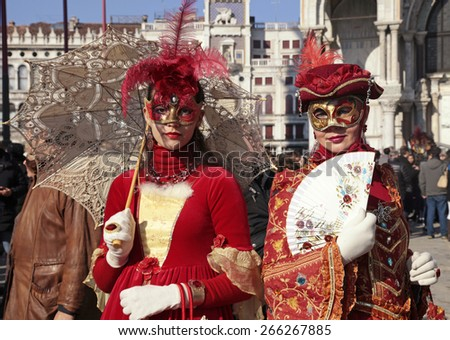 VENICE, ITALY - FEBRUARY 8, 2015: Two unidentified masked women in red costume on San Marco Square during the Carnival in Venice, Italy.  - stock photo