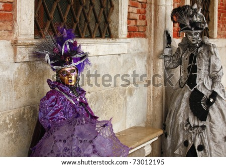 VENICE, ITALY  - FEBRUARY 28: Two unidentified people in costume in St. Mark's Square during the Carnival of Venice on February 28, 2011.  The 2011 annual carnival is held February 26 to March 8, 2011