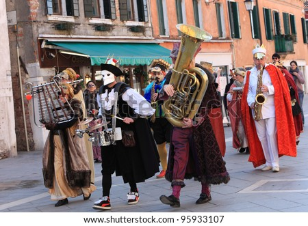VENICE, ITALY-FEBRUARY 26:Unidentified funny disguised people play instruments during a musical parade in the Carnival of Venice on February 26, 2011 in Venice, Italy. In 2012 the Carnival was between 11- 21 February. - stock photo