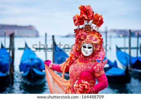 VENICE, ITALY - FEBRUARY 10: Unknown woman in red dress masked for traditional Venice Carnival in front of typical gondola boats, February 10, 2013 in Venice, Italy - stock photo