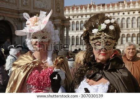 VENICE, ITALY - FEBRUARY 8, 2015: Women in venetian carnival costume posing at San Marco square, Carnival of Venice. - stock photo