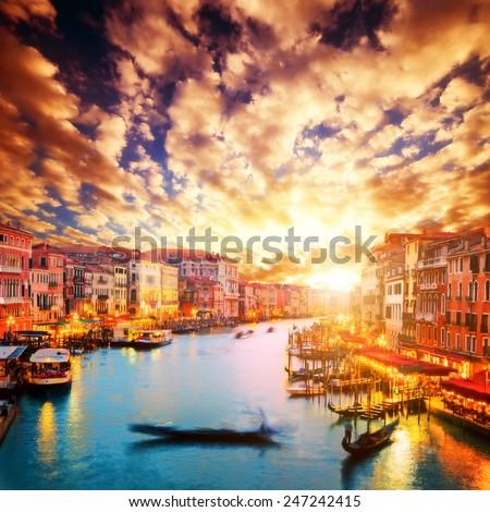 Venice, Italy. Gondola floats on Grand Canal at romantic sunset. View from Rialto Bridge - stock photo