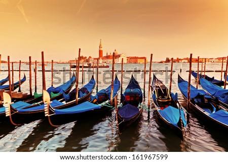 Venice, Italy. Gondolas on Grand Canal at sunset. San Giorgio Maggiore in the background - stock photo
