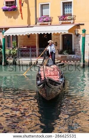 VENICE, ITALY - 26 JUNE, 2014: Gondolier rides gondola. The profession of gondolier is controlled by a guild, which issues a limited number of licenses - stock photo