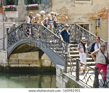 VENICE, ITALY - JUNE 6: tourists cross a canal on June 6, 2013 in Venice, Italy. Venice is one of the world's most popular tourist destinations with 21 million visitors per annum.  - stock photo