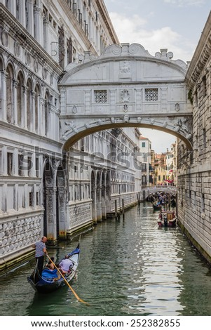Venice, Italy - June 27, 2014: Tourists sailing on gondolas  on water canal under Bridge of Sighs