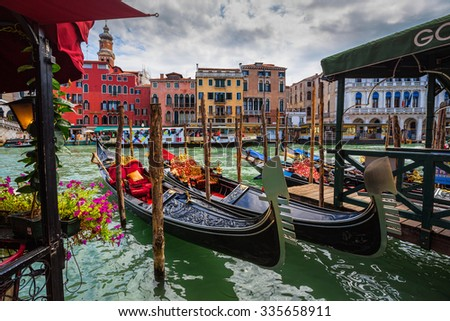 VENICE, ITALY - JUNE 26: Tourists travel on gondolas at canal on June 26, 2014 in Venice, Italy . Gondola trip is the most popular touristic activity in Venice. - stock photo