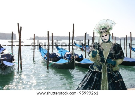 VENICE, ITALY - MARCH 6: An unidentified masked person stands in front of gondolas during the Venice Carnival on March 6, 2011 in Venice, Italy. The carnival is from February 26 - March 8, 2011. - stock photo