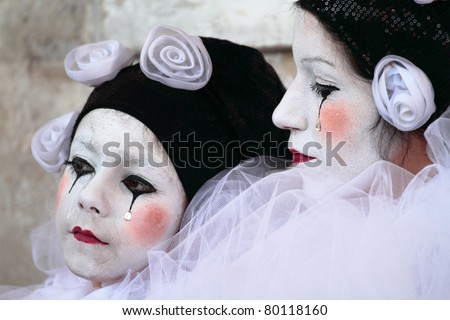 VENICE, ITALY - MARCH 7: An unidentified masked woman and child pose in front of St. Mark church in Venice, Italy on March 7, 2011 during the annual Venice carnival. The carnival is from February 26 - March 8, 2011.