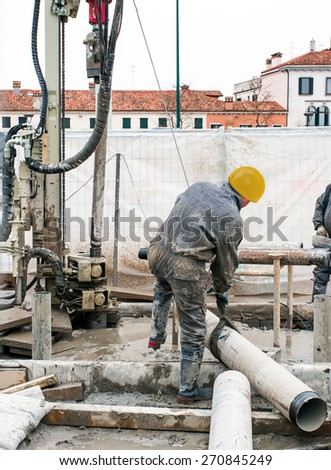 VENICE, ITALY - MARCH 21, 2015: in venice the water is underground, workers bring another tube to add in drilling,  - stock photo