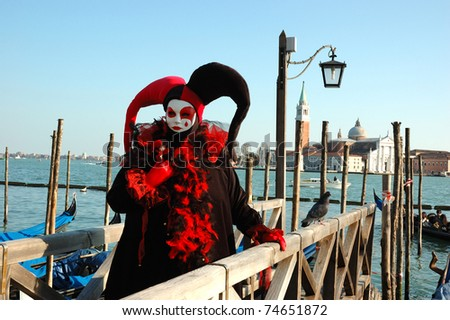 VENICE,ITALY - MARCH 8: Person in Harlequin mask near canal during the Carnival of Venice on March 8, 2011.The annual carnival was held in 2011 from February 26th to March 8th. - stock photo