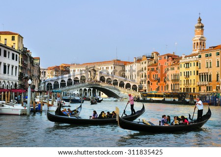 VENICE, ITALY - MAY 01 2011:Gondolas sail on the Grand Canal in Venice, Italy with the Rialto bridge in the background.About 30 million people visit the city each year. - stock photo