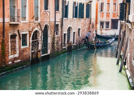 Venice, Italy - May 14, 2010: Gondolier leaning on the wall to propel the gondola on a turquoise canal turn. - stock photo