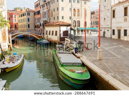 Venice, Italy - May 24, 2015: Men cleaners engaged in loading trash in a special barge morning in Venice. Removal garbage in Venice is only possible on the water.