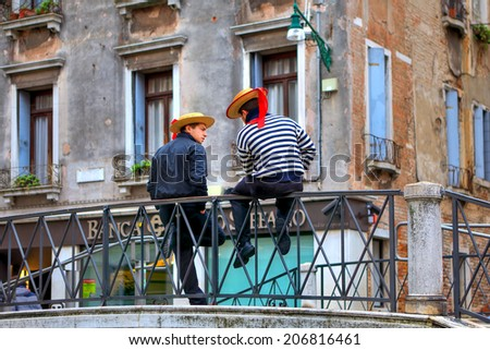 VENICE, ITALY - NOVEMBER 13, 2013: Gondoliers in traditional dress sitting on the bridge. Gondolier must be Venetian by birth, it is one of the oldest professions in the world controlled by a Guild. - stock photo