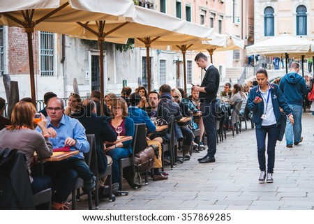 VENICE, ITALY - OCTOBER 11: People are sitting at the outside terrace of a small cafe in Venice, Italy