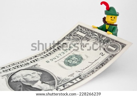 Venice, Italy - October 23, 2014: Robin Hood (as Lego figure) standing on  an American one dollar bill, October 23, 2014 in Venice, Italy - stock photo