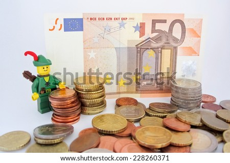 Venice, Italy - October 23: Robin Hood (as Lego figure) standing on  50 euro bill and European Euro coins, October 23, 2014 in Venice, Italy - stock photo