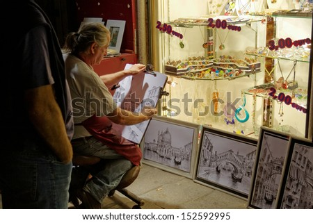 VENICE, ITALY - SEPTEMBER 5: A senior male artist at work in his studio, finishing up a freehand drawing of a Venice landmark on September 5, 2009 in Venice, Italy.