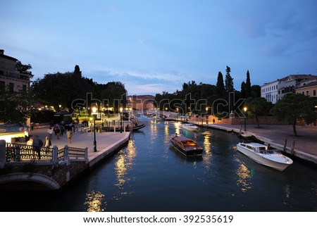 Venice, Italy - September 22, 2015: night view of venetian life beautiful illumination reflects in sea water summer time against clear sky on townscape background, horizontal picture - stock photo