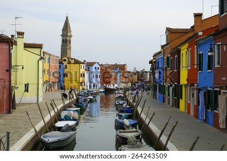 Venice, Italy, september 22th 2011, tourist and boats along the typical canal in Burano village in a sunny day - stock photo