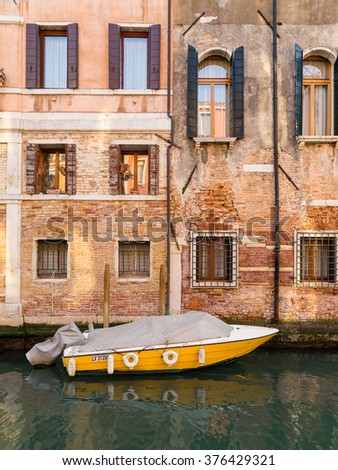 VENICE, ITALY - 13TH MARCH 2015: A view of old buildings along the Venetian Canals in the Cannaregio District of Venice. A boat can be seen. - stock photo