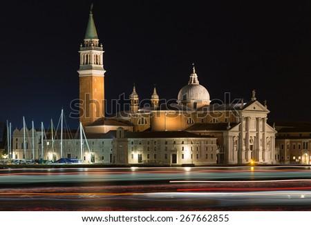 VENICE, ITALY - 13TH MARCH 2015: Church of San Giorgio Maggiore on San Giorgio Maggiore at night. Light trails can be seen in the water from boats - stock photo
