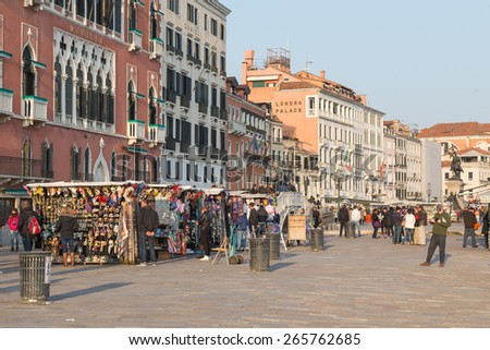 VENICE, ITALY - 13TH MARCH 2015: Part of Riva degli Schiavoni in Venice during the day, showing large amounts of people, building exteriors and market stalls - stock photo