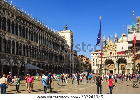 VENICE-JUN 2  2014: St Mark's Square in Venice, Italy. The Piazza is the central landmark and gathering place. Tourists enjoy Saint Mark Square on a spring day. More than 20 million people every year. - stock photo