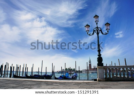 Venice lagoon. Gondolas moored by Saint Mark square with beautiful lamp post and San Giorgio di Maggiore church in the background. Venice, Italy, Europe         - stock photo