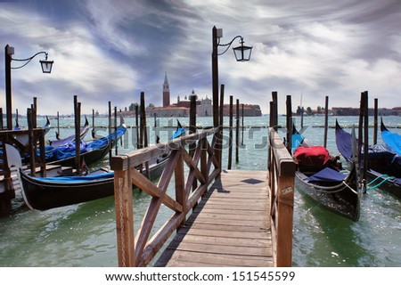 Venice lagoon. Gondolas moored by Saint Mark square with San Giorgio di Maggiore church in the background. Venice, Italy, Europe - stock photo