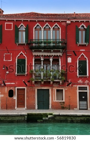 Venice: lovely 15th Century red palace, with gothic windows and balconies with flowers. Venezia, Italy. - stock photo