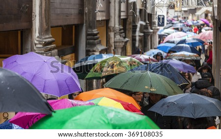 VENICE-MAR 02: Crowd of people with umbrellas walking in the rain in a narrow Venetian street on March 02,2014 in Venice, Italy, during the Carnival days.