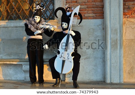 """VENICE-MAR 7:Two unidentified masked person in """"Musician"""" costume at St. Mark's Square during the Carnival of Venice March 7, 2011 in Venice.The 2011 carnival was held from February 26th to March 8th. - stock photo"""