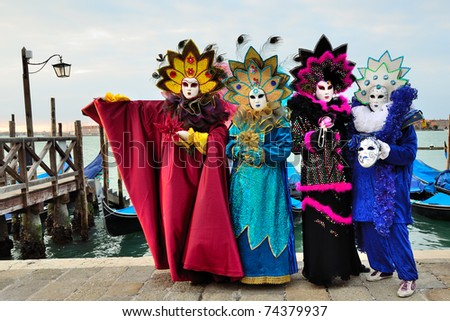 VENICE - MARCH 7: Four unidentified masked persons in costume in St. Mark's Square during the Carnival of Venice on March 7, 2011 in Venice. The 2011 carnival was held from February 26th to March 8th. - stock photo